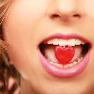 girl eating a heart-shaped candy