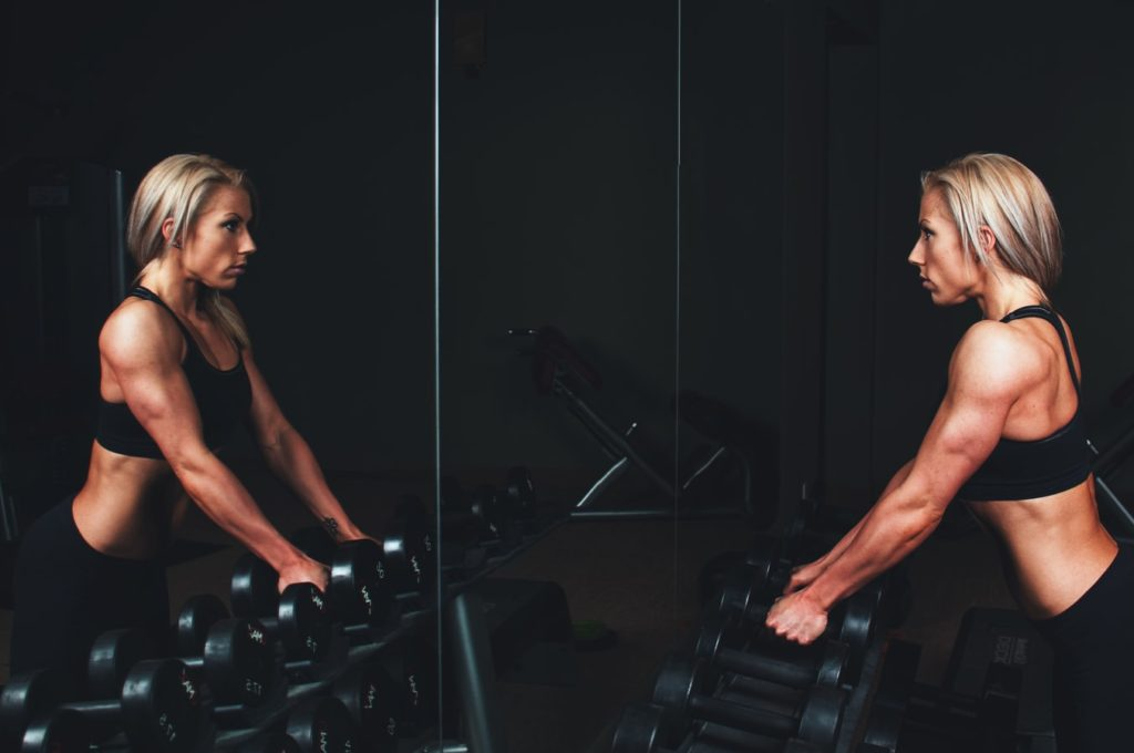 bodybuilder female looking at her self in the mirror while lifting dumbbells
