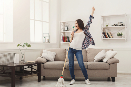 woman dancing and singing in her living room using a broom