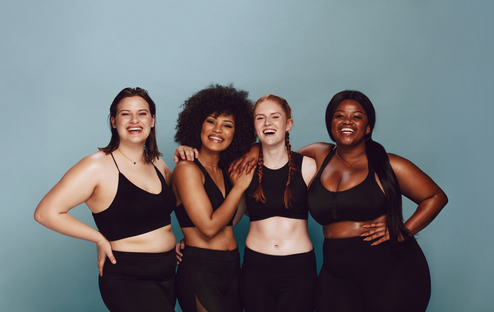 four smiling women with different body shapes and types